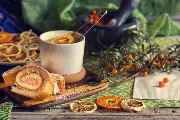 Copo do chá, um biscoito, bagas e frutas secadas na tabela. estilo vintage