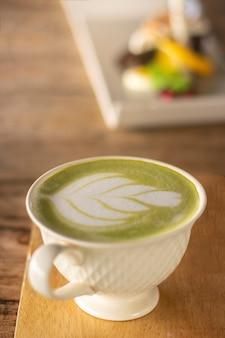 Copo do chá verde de matcha latte no fundo de madeira escuro.