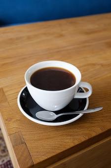 Copo do cofffee preto na tabela de madeira, café da manhã.