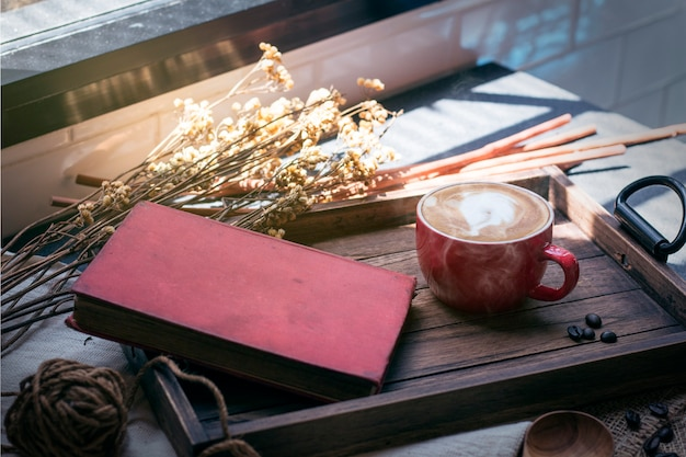 Copo do latte, feijão de café na bandeja de madeira com manhã morna.