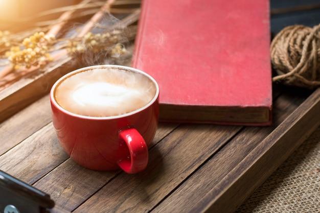 Copo do latte, livro na bandeja de madeira com luz morna da manhã perto da janela.