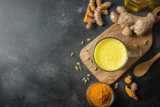 Copo do leite de açafrão dourado indiano com pó da curcuma e ingredientes no preto. vista de cima.