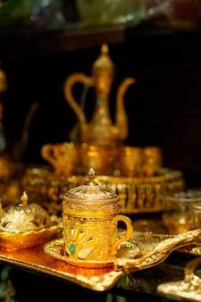 Copo e bule árabes do ouro no mercado oriental. chá oriental