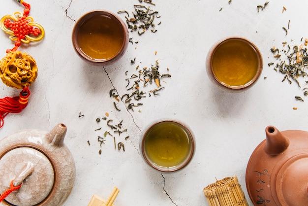Copo e bule cerâmicos da argila chinesa tradicional com chá erval