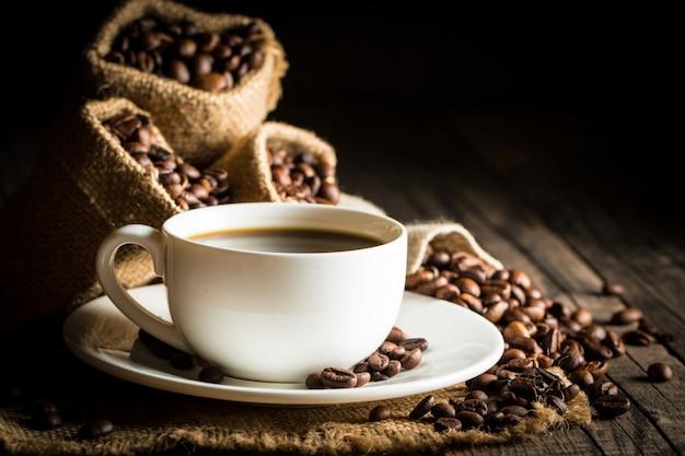 Copo e feijões de café em um fundo rústico.