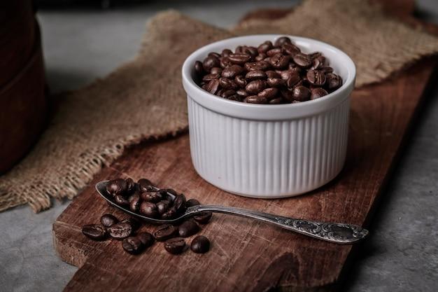 Copo e feijões de café na mesa de cozinha velha.
