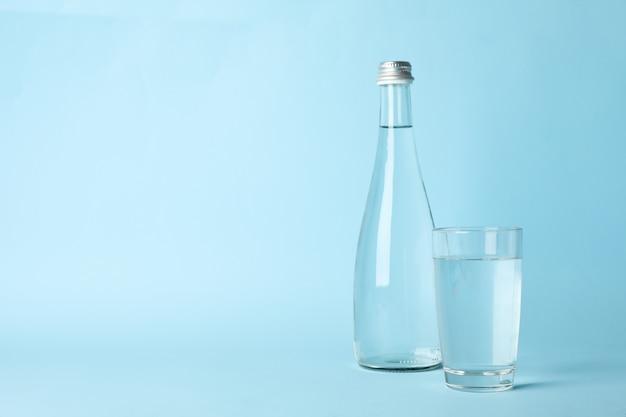 Copo e garrafa com água em azul, espaço para texto