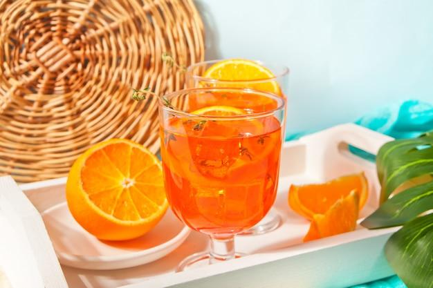 Copo e garrafa com chá gelado doce caseiro de laranja ou coquetel, limonada com tomilho. bebida refrescante e fria. festa de verão.