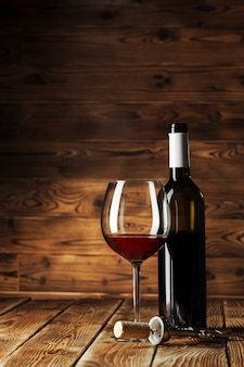 Copo e garrafa com delicioso vinho tinto na mesa contra a madeira