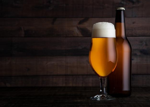 Copo e garrafa de cerveja dourada com espuma no fundo da mesa de madeira