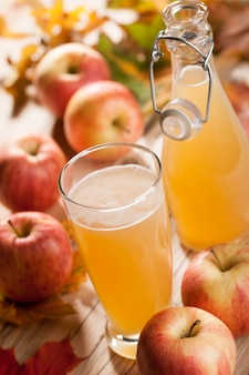 Copo e garrafa de suco de maçã, maçãs, folhas caem na mesa de madeira