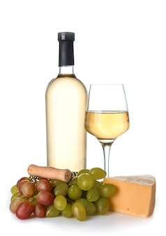 Copo e garrafa de vinho com queijo na superfície branca