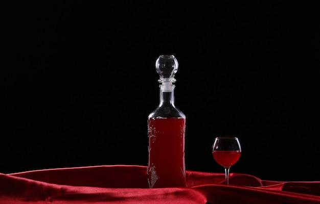 Copo e garrafa de vinho em uma seda de fundo escuro