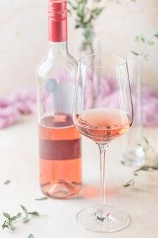 Copo e garrafa de vinho rosé sobre fundo claro.