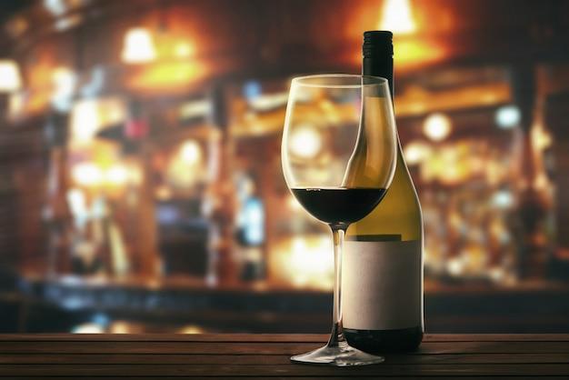 Copo e garrafa de vinho tinto em uma mesa em um restaurante