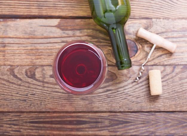 Copo e garrafa de vinho tinto na mesa de madeira
