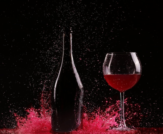 Copo e garrafa de vinho tinto splash em preto
