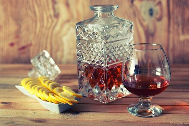 Copo e jarra com álcool de conhaque