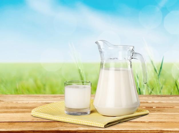 Copo e jarro de leite com prado verde no fundo