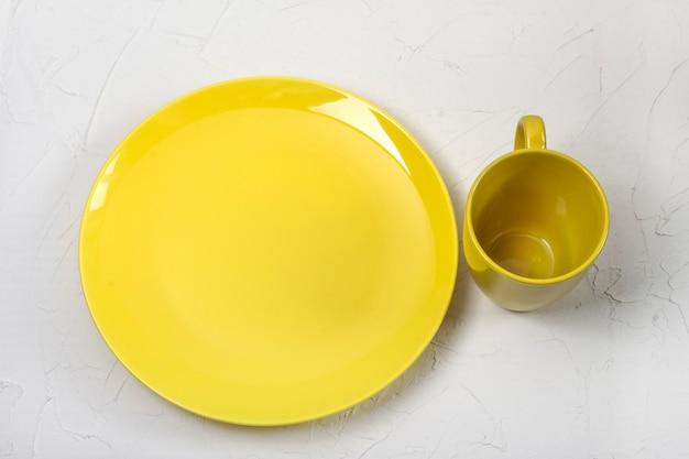 Copo e prato amarelos em uma cor da moda, sobre um fundo branco.