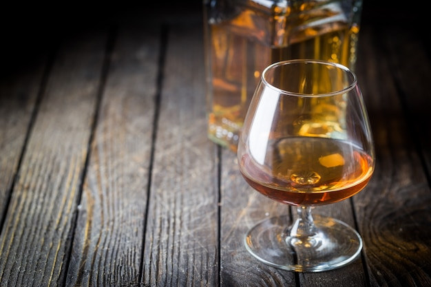 Copo e uma garrafa de conhaque ou conhaque na mesa de madeira.