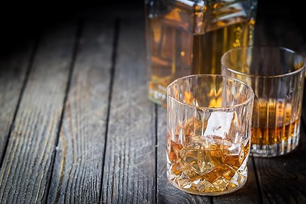 Copo e uma garrafa de uísque com gelo na mesa de madeira escura