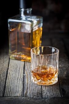 Copo e uma garrafa de uísque na mesa de madeira escura