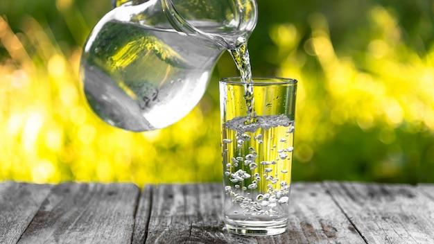 Copo e uma jarra de água na mesa de madeira