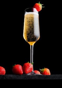 Copo elegante de champanhe amarelo com morango em cima e frutas frescas na placa de mármore preta no preto.