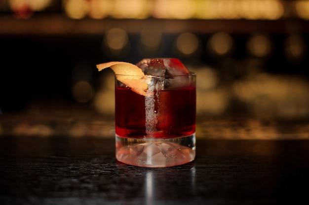 Copo elegante de saboroso coquetel de uísque fresco e forte decorado com casca de laranja no balcão do bar