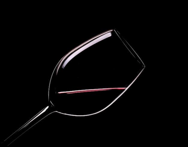 Copo elegante de vinho tinto em um fundo preto