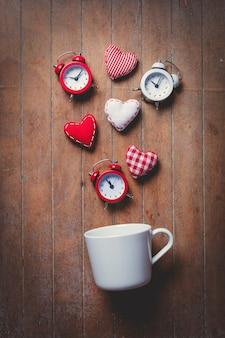 Copo em deitado de lado com despertadores e formas de coração