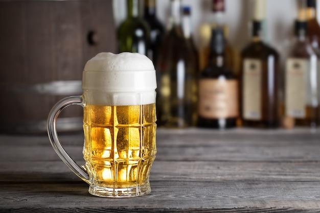 Copo grande de cerveja light com espuma no balcão de bar