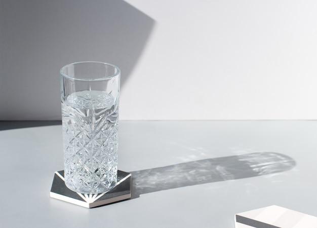 Copo lapidado de água limpa e fresca com sombra na mesa cinza, cópia espaço, luz forte. bebida mineral refrescante de verão, bebida gelada e saudável para hidratação. água cristalina