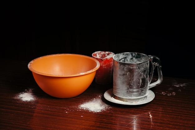 Copo laranja, copo medidor e uma peneira de aço estão sobre uma mesa de madeira em preto