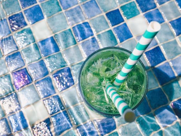 Copo lindo com um coquetel refrescante no fundo da piscina