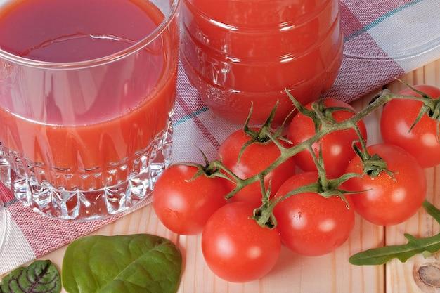 Copo meio cheio com suco de tomate com polpa em uma mesa