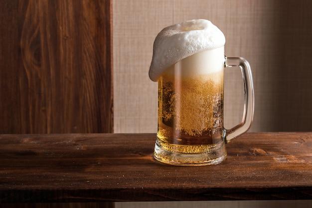 Copo meio vazio de cerveja na mesa de madeira