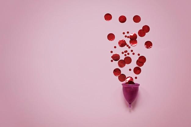 Copo menstrual com partículas vermelhas na superfície rosa