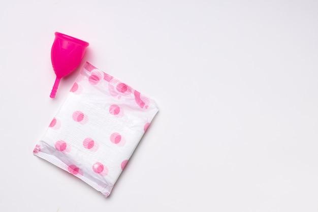 Copo menstrual e almofada higiênica sobre fundo de papel