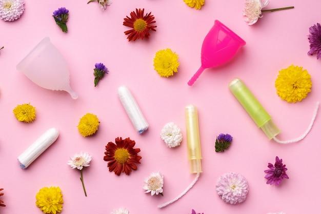 Copo menstrual e tampões na vista superior do plano de fundo com padrão floral