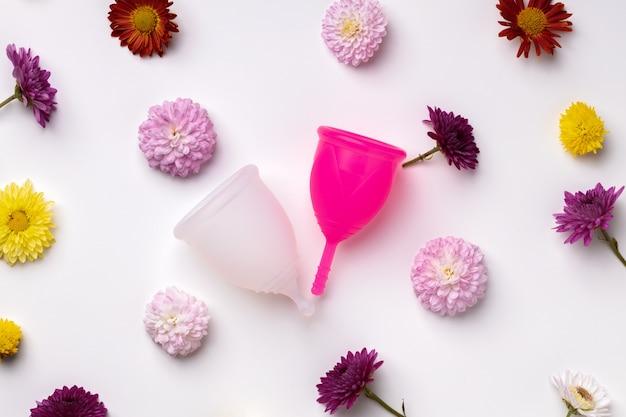 Copo menstrual na vista superior do plano de fundo com padrão floral, espaço de cópia
