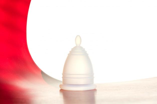 Copo menstrual reutilizável branco sobre um fundo branco-vermelho.