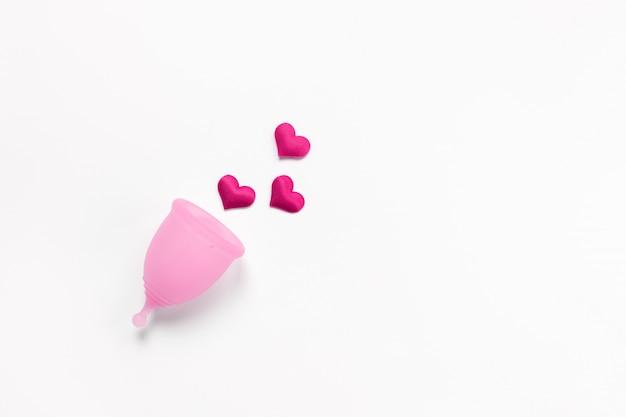 Copo menstrual rosa sobre fundo branco com corações vermelhos