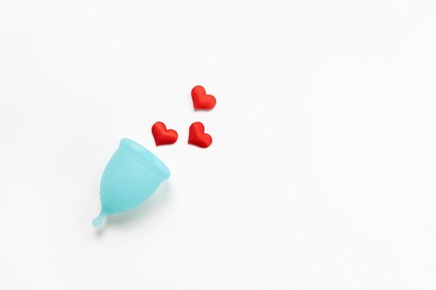 Copo menstrual turquesa sobre fundo branco, com corações vermelhos. conceito zero desperdício, economia, minimalismo, nos dias de hoje. produto de higiene feminina, configuração plana, cópia espaço. horizontal