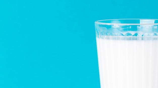 Copo minimalista de leite e fundo azul com espaço de cópia