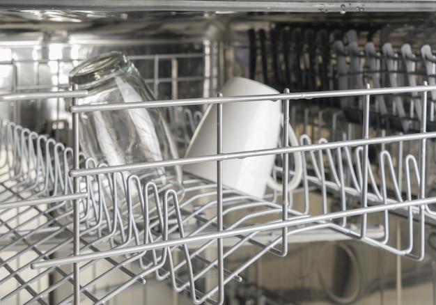 Copo molhado e caneca branca na máquina de lavar louça