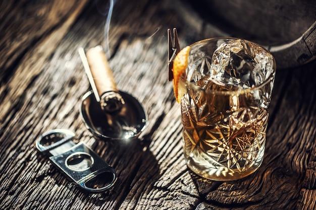 Copo ornamental cheio de uísque e gelo em uma madeira vintage ao lado de um cortador de charutos e um charuto aceso.