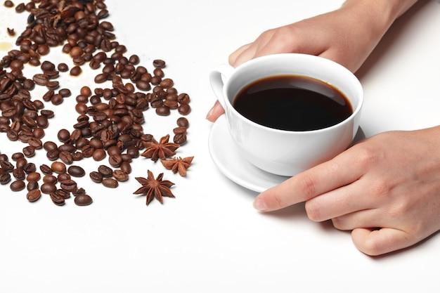 Copo pequeno cheio de feijão de café, isolado no branco