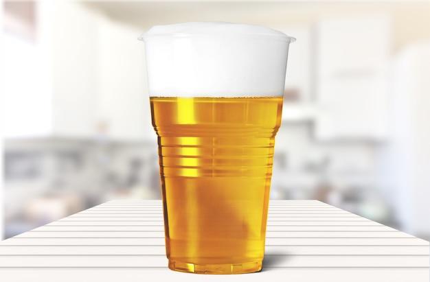 Copo plástico com cerveja na mesa